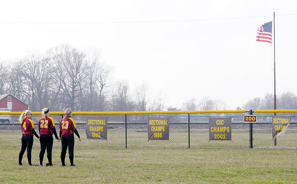 Don Knight | The Herald Bulletin<br /> Alexandria's outfielders, from left, Emmy Gaines Stacie Farmer and Kaitlyn Davis face the flag as the National Anthem is played before the Tigers played Muncie Central on Tuesday. Find out how the Tigers played in today's local sports roundup.