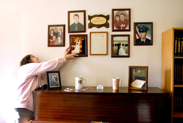 John P. Cleary | The Herald Bulletin<br /> Lisa Keefe, Rebecca Sperry's mother, puts back up Rebecca's wedding photo with other Keefe family photos.