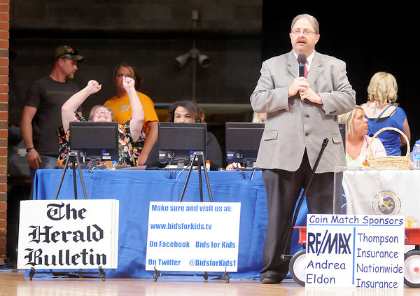 Don Knight   The Herald Bulletin<br /> Pete VanBaalen stands in front of a bank of volunteers taking bids over the phone as he emcees the Bids for Kids Auction. The Bids for Kids annual auction to raise funds for the Exchange Club Family Resource Center for child abuse prevention continues today from 10 a.m. to midnight in Anderson University's Reardon Auditorium. To bid on items, attend the event at Reardon or call 641-3737. You can watch the event on Comcast channel 3 or bidsforkids.tv. To view or buy this photo and other Herald Bulletin photos, visit heraldbulletin.smugmug.com.