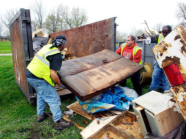 John P. Cleary   The Herald Bulletin<br /> City employees load up trash into a dumpster that was brought to Athletic Park Monday afternoon for disposal as the Rev. JT Menifee Citywide Clean Up campaign kicked off Monday and will run for three weeks this year.
