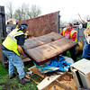 John P. Cleary | The Herald Bulletin<br /> City employees load up trash into a dumpster that was brought to Athletic Park Monday afternoon for disposal as the Rev. JT Menifee Citywide Clean Up campaign kicked off Monday and will run for three weeks this year.