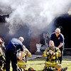 John P. Cleary | The Herald Bulletin<br /> Anderson firefighters get fresh air tanks as they battled a smoky blaze in the 2600 block of Highland Road Tuesday morning.