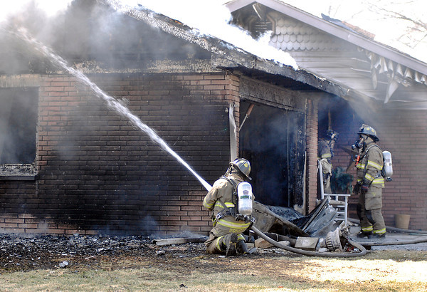 John P. Cleary | The Herald Bulletin<br /> Anderson firefighters battled a house fire Tuesday morning in the 2600 block of Highland Road that destroyed the garage and did heavy smoke damage to the rest of the house.
