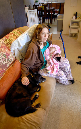 John P. Cleary | The Herald Bulletin<br /> Rebecca Sperry, with Autumn in her arms, pets her dog Mandy as she sits in the living room.