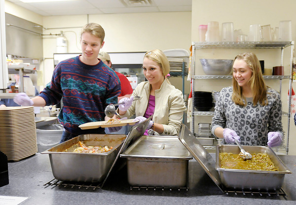 Don Knight   The Herald Bulletin<br /> From left, Anderson University students Ian Oechsle, Mallory Teskey and Kylie Kantner serve the evening meal at The Christian Center on Friday.