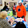 John P. Cleary | The Herald Bulletin<br /> Willie Turner checks out information from the Indiana Child Support Bureau during the Anderson Township Trustee Resource Fair held Friday.