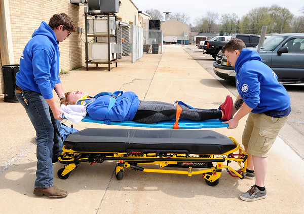 Don Knight | The Herald Bulletin<br /> From left, EMT students Sam Hudson, Michelle Hockema and Emma Simer demonstrate moving a patient at D26 on Thursday.