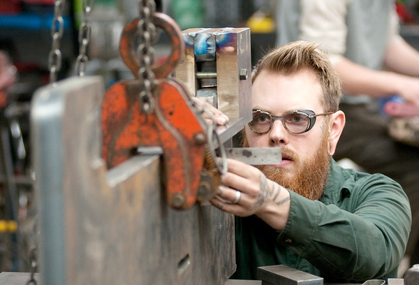 Don Knight | The Herald Bulletin<br /> Nathan Brandt checks that a piece of metal is square before tack welding it  while making a press at Coal Ironworks in Anderson.
