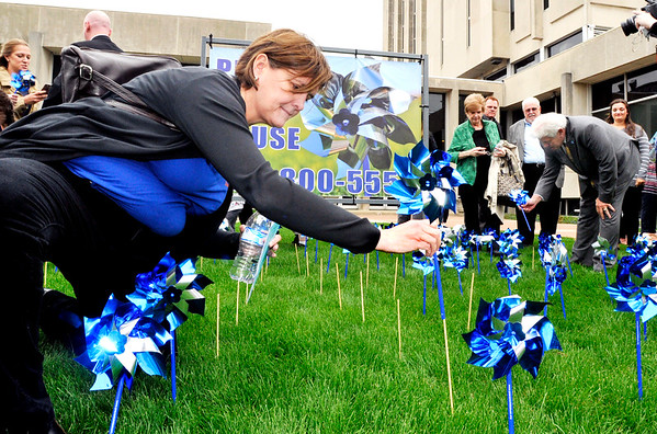John P. Cleary    The Herald Bulletin<br /> Terri Parke, of the Children's Bureau, places her pinwheel in the pinwheel garden on the front lawn of the Anderson City Building Monday as part of the kick-off of the Prevent Child Abuse Awareness Month in Madison County.