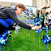 John P. Cleary |  The Herald Bulletin<br /> Terri Parke, of the Children's Bureau, places her pinwheel in the pinwheel garden on the front lawn of the Anderson City Building Monday as part of the kick-off of the Prevent Child Abuse Awareness Month in Madison County.