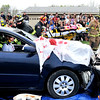 John P. Cleary |  The Herald Bulletin<br /> Lapel/Stony Creek Fire Department personnel take one victim away to an ambulance while rescuers work to extricate another victim during this mock accident for a Lapel High School drunk driver education awareness program held Friday.