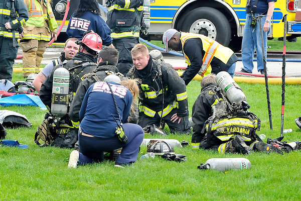 John P. Cleary |  The Herald Bulletin<br /> Firefighters take a break to get their air packs changed out after battling a structure fire in the 4600 block of State Road 32 East in Chesterfield Monday morning.