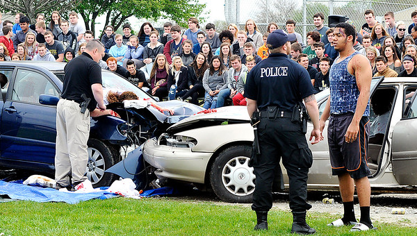 John P. Cleary |  The Herald Bulletin<br /> Lapel police go through the procedures of investigating this mock accident as Lapel High School students look on. The school held a drunk driver education awareness program Friday complete with a fatal car crash.