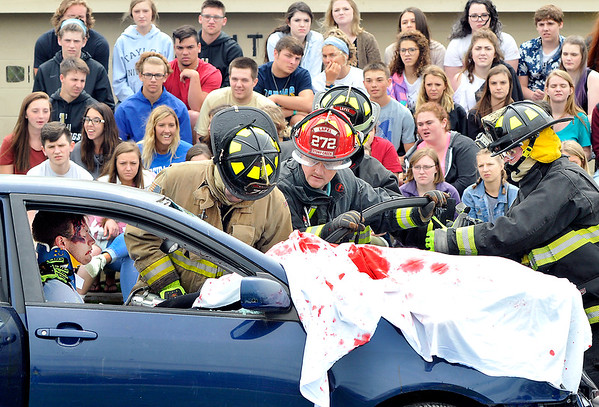 John P. Cleary    The Herald Bulletin<br /> Lapel/Stony Creek Fire Department personnel work to extricate this person from the car in this mock accident scene as Lapel High School students watch.  Lapel High School held a drunk driver education awareness program Friday complete with a fatal car crash.