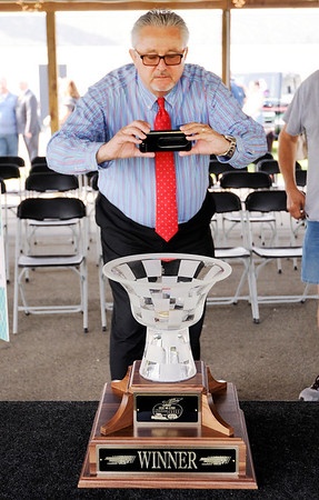Don Knight | The Herald Bulletin<br /> Wayne Westgate with Pay Less takes a photo of the trophy for the Little 500 created by Prestige Art Glass in Elwood during a press conference at the Anderson Speedway on Wednesday.