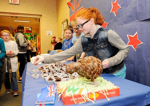 Don Knight | The Herald Bulletin<br /> Christina Peek places small plastic forks in samples of chocolate cake during Frankton Elementary's World's Fair on Thursday.
