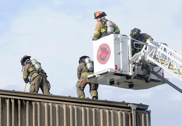 Don Knight | The Herald Bulletin<br /> AFD fire fighters get on to the roof at the former Church of Christ on Lindberg Road as they overhaul the building after extinguishing a fire on Wednesday.