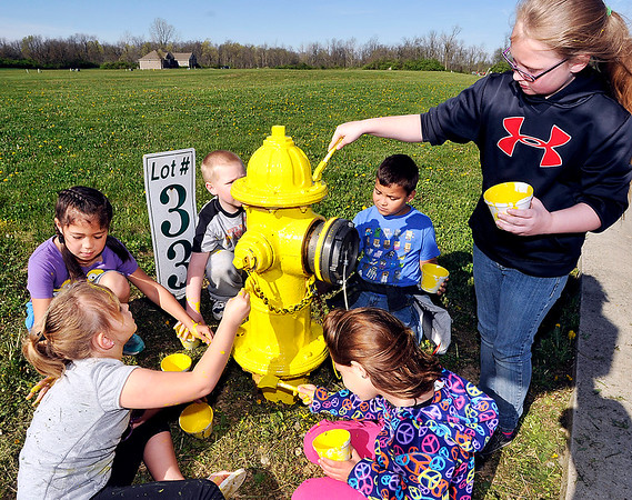 John P. Cleary |  The Herald Bulletin<br /> Students from Carrie Bowman's second-grade class from Elwood Elementary School paint the fire hydrants located in Cattail Estates in Elwood Tuesday. Bowman's class wanted to do a public service project and after contacting the mayor's office the hydrant painting was something the students took on as their project.