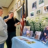 John P. Cleary |  The Herald Bulletin<br /> Carol Arena and Kelley Morgan, Mounds State Park Interpretive Naturalist, look over photos of Pete Domery and his dog Boomer at a informal memorial for Domery Saturday after he pasted away recently. Domery was a Mounds volunteer and park enthusiast and a nature photographer.