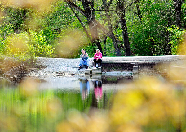 John P. Cleary    The Herald Bulletin<br /> The budding foliage of spring help frame these folks as they enjoy a nice afternoon sitting along the water at Shadyside Park Monday.