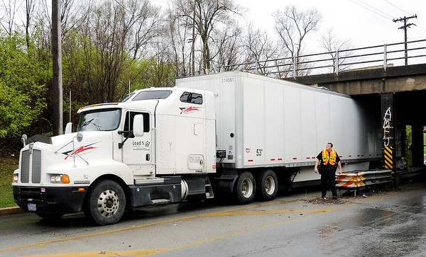 Don Knight | The Herald Bulletin<br /> A semi traveling north on Main Street got stuck under the train overpass on Wednesday. Two of the trailer's rear tires were deflated to lower it so that the truck could drive out from under the overpass.