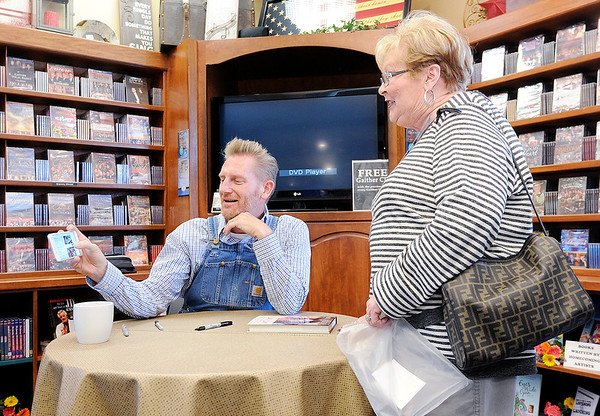 "Don Knight | The Herald Bulletin<br /> Rory Feek shares family photos with Sharon Starr before signing her copy of his book ""This Life I Live"" at Gaither Family Resources in Alexandria on Saturday. Feek's wife Joey was born and raised in Alexandria and the two enjoyed a successful music career before she lost her battle with cancer last year. In the book Rory talks about growing up, his love for Joey, their faith in God and saying goodbye."