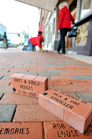 John P. Cleary    The Herald Bulletin<br /> Shannon Swain, of M.K. Betts, works to install five more commemorative bricks to the Walk of Stars in front of the Paramount Theatre Tuesday.
