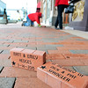 John P. Cleary |  The Herald Bulletin<br /> Shannon Swain, of M.K. Betts, works to install five more commemorative bricks to the Walk of Stars in front of the Paramount Theatre Tuesday.