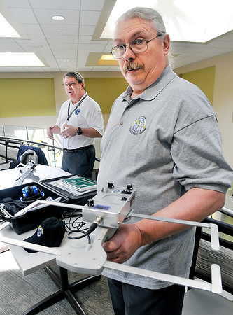 John P. Cleary | The Herald Bulletin<br /> As Lew Baker scans the room with one of the Project Lifesaver receivers, Jeff Byer, background, EMA communications, explains how the system works and how it would be used to help find loved ones who have wondered away from caregivers.