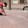 "Don Knight | The Herald Bulletin<br /> Aaron Kress writes ""Gone But Never Forgotten"" in chalk on the Dickmann Town Center park stage during a Chalk Walk for Justice for one-year-old Harlan Haines."