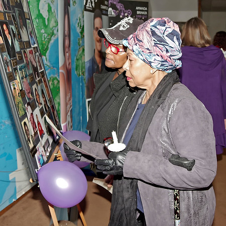 Mark Maynard | for The Herald Bulletin<br /> Vinnie James and Allonia Lynch pause to look at photos of homicide victims during the Annual Candlelight Vigil, which was presented as part of National Victims' Rights Week.