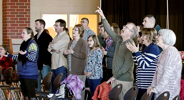 Mark Maynard | For The Herald Bulletin<br /> Harvest Bible Chapel congregants join in a song of worship during Palm Sunday services held at Anderson High School.