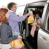 Don Knight | The Herald Bulletin<br /> From left, Amanda Bridges and Joan Heiden hand out bags of Easter Eggs at First Baptist Church on Saturday. Due to soggy grounds and inclement weather the church improvised and turned their Easter Egg hunt into a drive through.