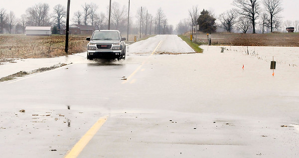 John P. Cleary | The Herald Bulletin<br /> This is on County Road 500W at the intersection of 600N where water is flowing across a large part of the roadway Tuesday afternoon.