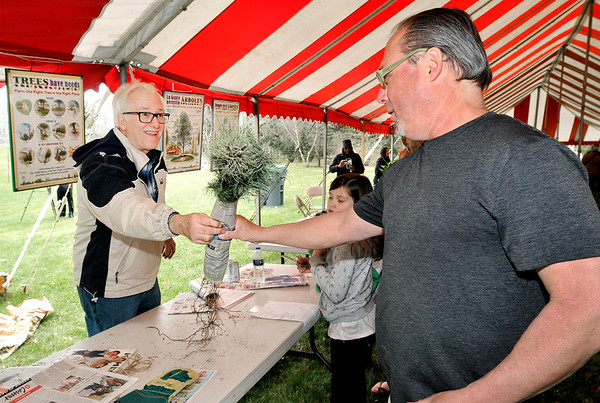 John P. Cleary   The Herald Bulletin  <br /> Volunteer Blake Janutolo gives Allan Ward two White Pine seedlings during <br /> ArborFest celebration activities Saturday.