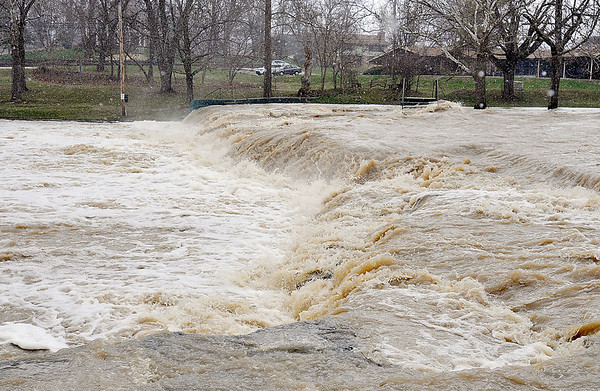 John P. Cleary | The Herald Bulletin<br /> The raging waters of Fall Creek kick up a spray as it roars past the falls and  downstream through Falls Park in Pendleton Wednesday afternoon after heavy rains hit the county hard Tuesday.