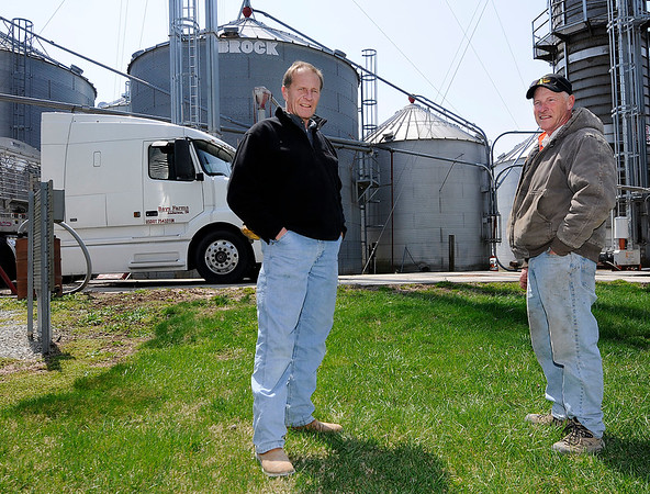 Don Knight | The Herald Bulletin<br /> Brian Bays, left, and his brother Allen stand in front of their grain silos at Bays Farm west of Anderson on Wednesday. The Indiana Soybean Alliance says one in every three rows planted in soybeans are currently being exported to China.