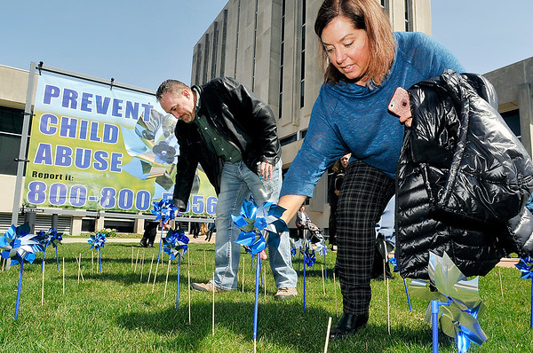 John P. Cleary | The Herald Bulletin  <br /> David and Shelley Dodd place their pinwheels in the pinwheel garden on the front lawn of the Anderson City Building Thursday during the kickoff of National Child Abuse Prevention Month.