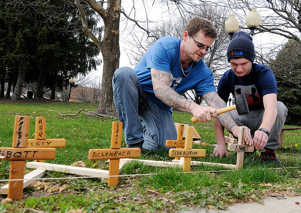 Don Knight | The Herald Bulletin<br /> From left, Aron Smith and Nate McTaggart install wooden crosses at Citizen's Plaza Park  in memory of victims of homicide or death by impaired drivers.