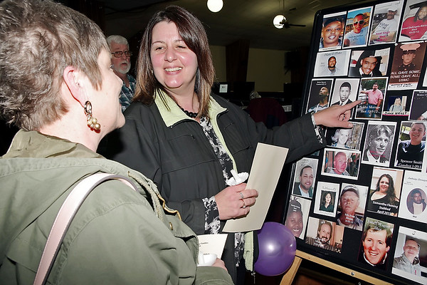Mark Maynard | for The Herald Bulletin<br /> Beth Morrow points out a photo of her deceased brother, Bobby, to Karin Reichart at the Annual Candlelight Vigil for Survivors of Homicide and Impaired Driving Friday evening at the Aletheia Fellowship and Ministry Center.