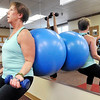 John P. Cleary | The Herald Bulletin<br /> Karen McGee, patient registration, works with hand weights and a giant ball during St. Vincent Anderson fitness class for employees.