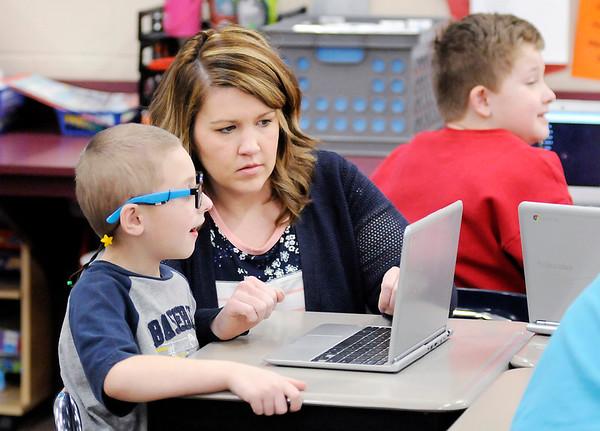Don Knight | The Herald Bulletin<br /> Meghan Hersberger helps Finnley Toney log onto an online quiz at Frankton Elementary School on Friday.