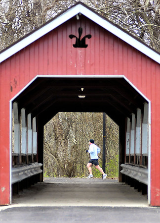 John P. Cleary | The Herald Bulletin  <br /> This jogger is framed  by the covered bridge as he makes his way along the trails around Shadyside Lake Tuesday afternoon.