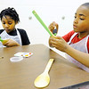 Don Knight | The Herald Bulletin<br /> From left, Alaiyha Campbell and Drayden White paint spoons that will be used as plant markers at the Impact Center on Saturday.