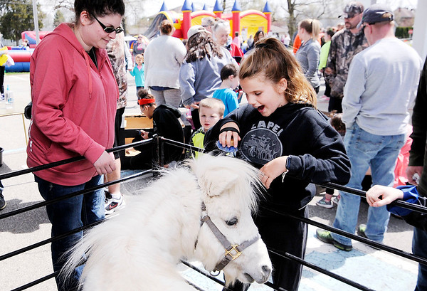 Don Knight | The Herald Bulletin<br /> Jordan Pilkington, 11, brushes Sam, a miniature horse from Scheumann Farm, during Daybreak Community Church's Easter Egg Hunt in Lapel on Saturday.