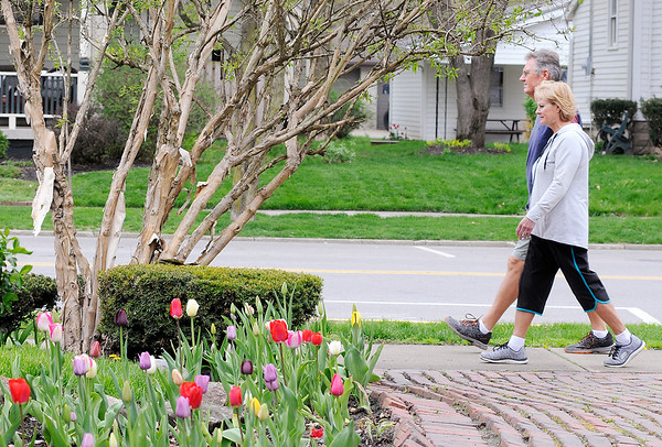 Don Knight   The Herald Bulletin<br /> Walkers pass by tulip bulbs in bloom at Falls Park in Pendleton on Tuesday. The work week forecast is calling for a chance of rain on Wednesday and Thursday.