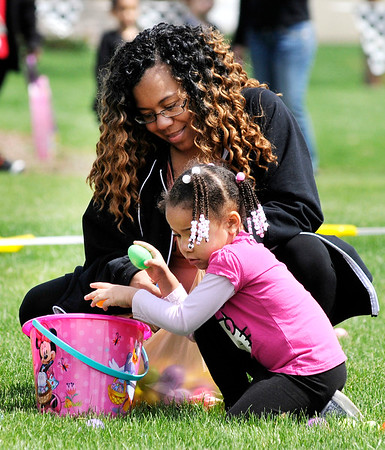 Don Knight | The Herald Bulletin<br /> Zendaya Gaines, 3, picks up candy-filled Easter Eggs with help from her mother Nakisha Shelton during Daybreak Community Church's Easter Egg Hunt in Lapel on Saturday.