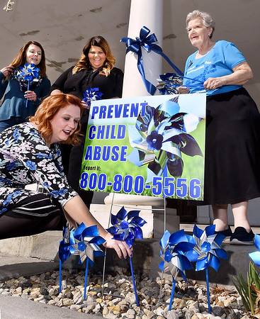 John P. Cleary | The Herald Bulletin <br /> Stephanie Fertucci, director of the Children's Bureau, plants a pinwheel as Carrie Frauhiger, Children's Bureau intern; Hannah Burke, Children's Bureau assistant director; and Bonny Clark, Anderson Noon Exchange Club program coordinator, look on waiting with more pinwheels. This was part of the kickoff luncheon for National Child Abuse Prevention Month Tuesday at the Edgewood Golf Course and Event Center.