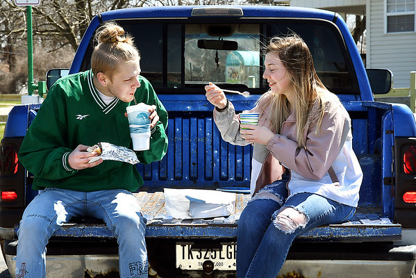 John P. Cleary | The Herald Bulletin <br /> With sunshine and warming temperatures, Dakota McCulloch and Kendra Jackson enjoy a tailgate lunch, including ice cream, Tuesday afternoon at Frazier's Dairy Maid. Frazier's opened Monday,April first, for the season.