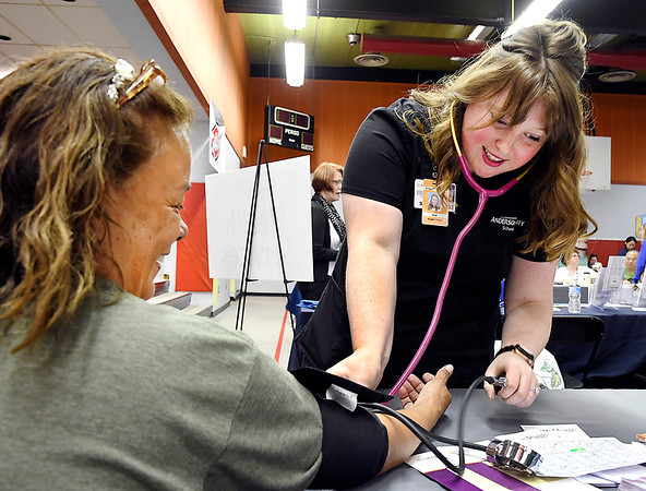 John P. Cleary | The Herald Bulletin <br /> Nina Soria gets her blood pressure checked by Anderson University student nurse Sarah Drake at the Community Hospital Anderson table Wednesday during the Madison County Community Connect event  held at the Anderson Impact Center.